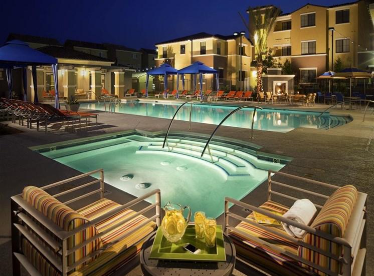 Illuminated hot tub and pool, outdoor furniture, and cabanas at night