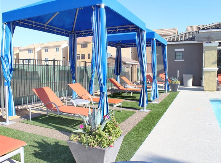 Poolside cabanas with lounge chairs on a sunny day