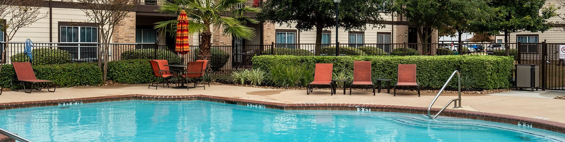 Pool with lounge chairs at La Sierra Apartments