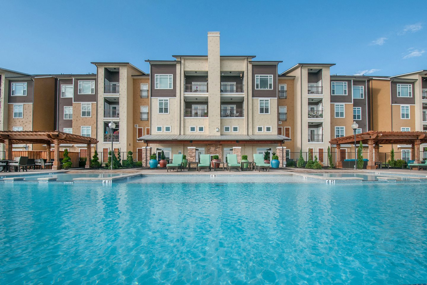 Pool view with apts building in background Waco, TX Apartments l Luxe at 1300