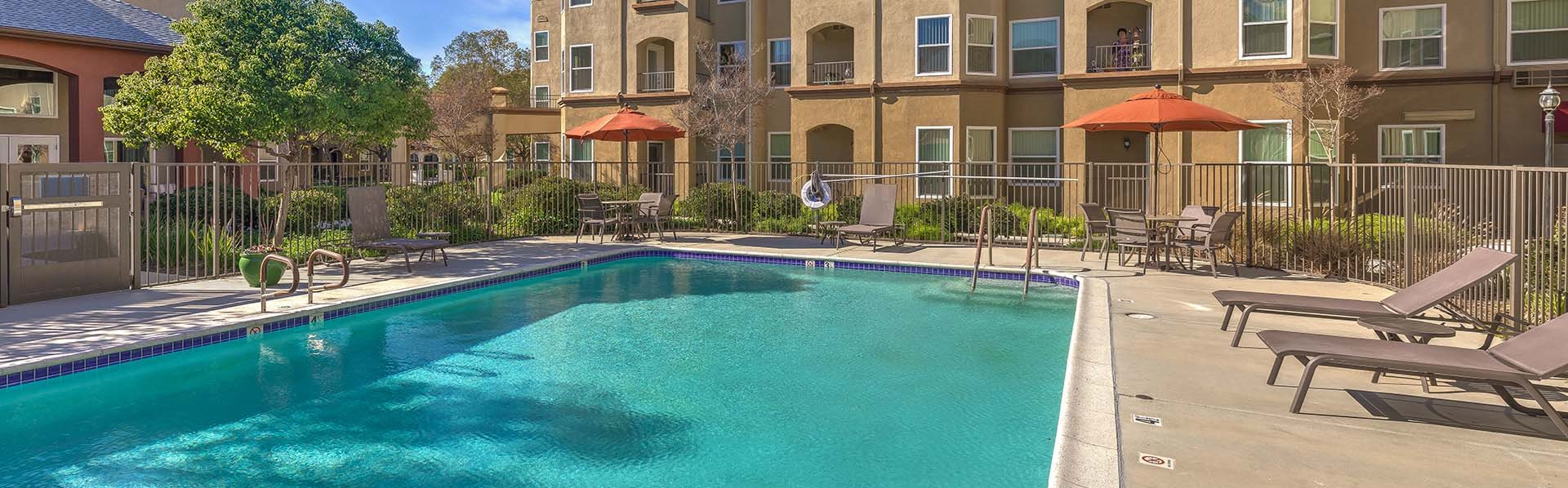 Pool with lounge chairs  l Vintage at Bouquet Canyon Senior Apartments
