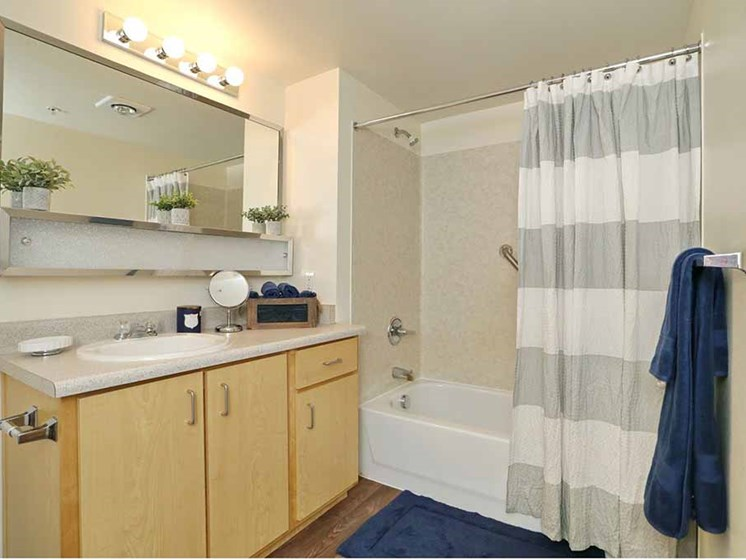 Apartments for Rent in Everett-Vintage At Everett Apartments Bathroom With Square Tile And Tub And Vanity Lighting