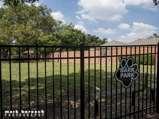 Fenced in Dog Park with lots of grass and shade.