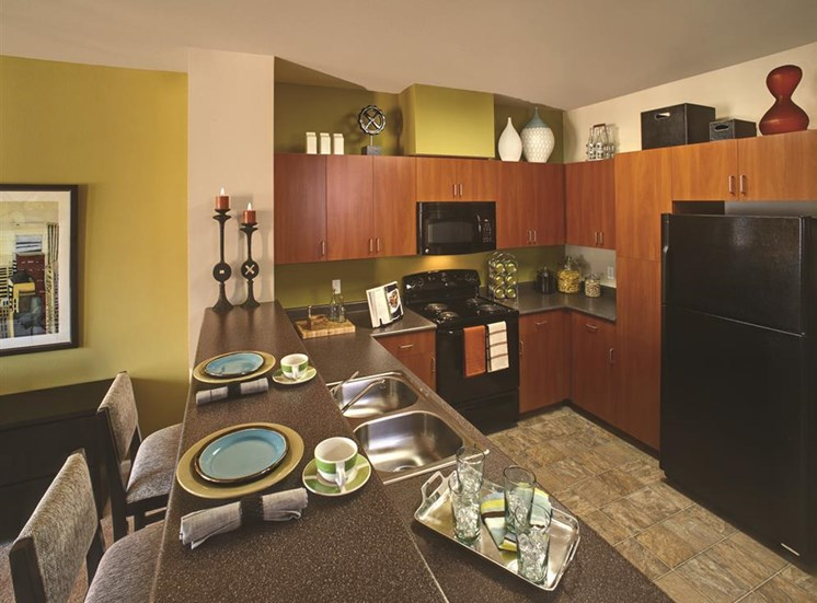Kitchen featuring black appliances and granite inspired countertops at Sanctuary Apartments in Renton, WA