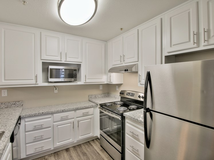 Kitchen with stainless steel appliances, quartz counters, and white cabinets.