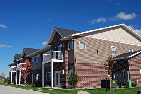 exterior of moorhead apartment, blue sky, green grass