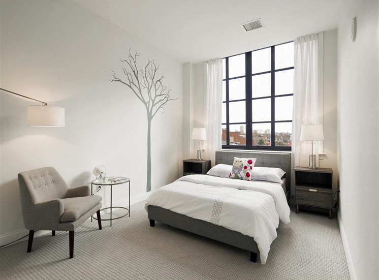 spacious master bedroom with large window including view of city
