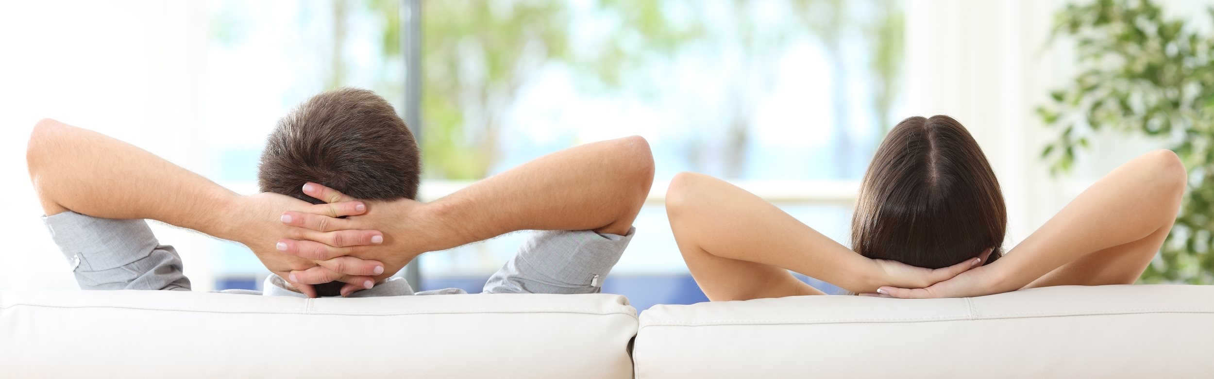 Couple Relaxing on Couch with Hands Behind Head