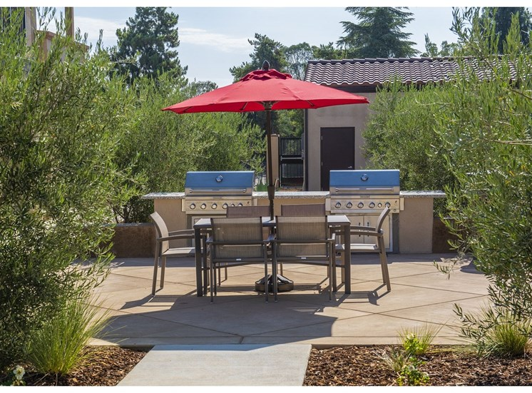 Common Courtyard Area With Table and Umbrella at Tempranillo Apartment Homes