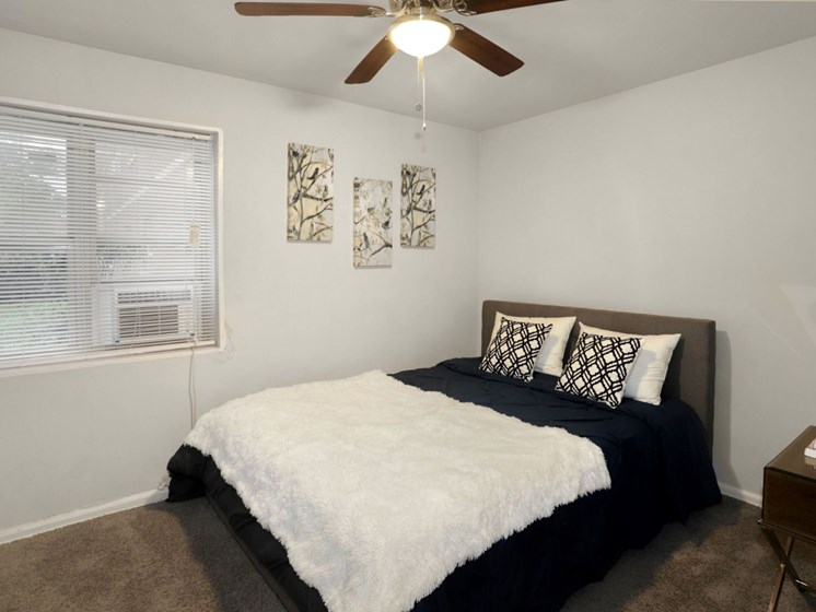 furnished bedroom with ceiling fan and window AC