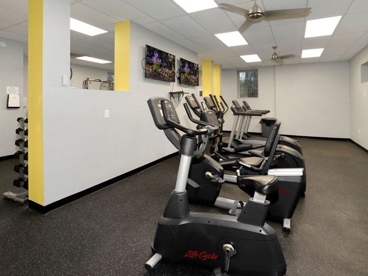 gym room with cardio equipment and TVs