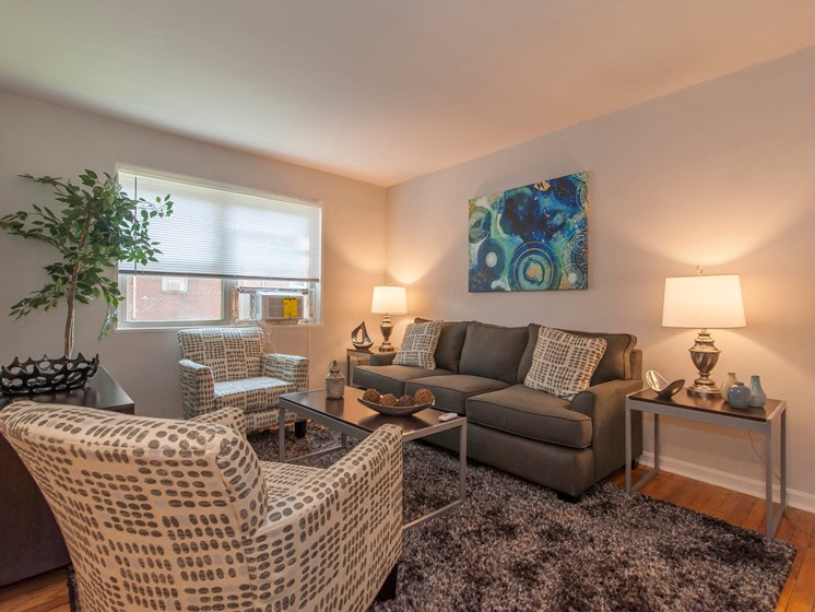 fully furnished hardwood floor living room with windows