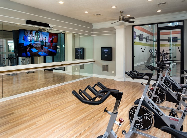 Fitness center picture with bike machines, tv and mirror