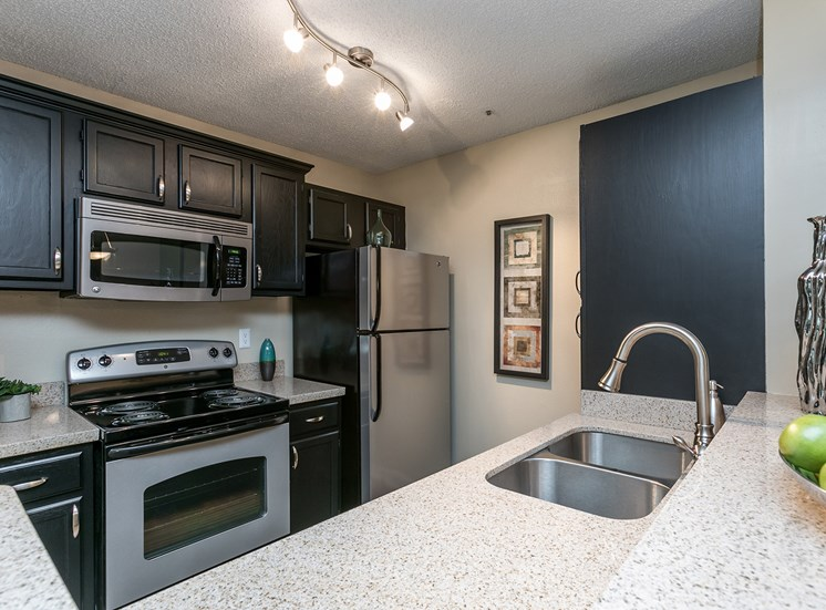 kitchen in model apartment with stainless steel appliances and granite countertops