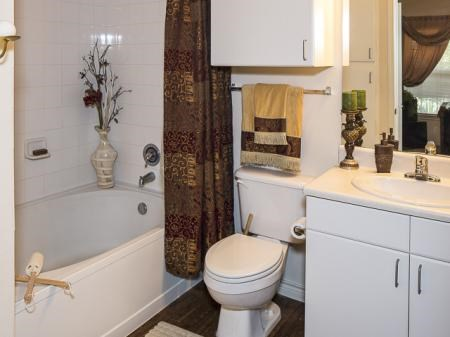 Bathroom with garden style bath tub, additional cabinet located above toilet,  and decorative towels on towel holder underneath cabinet