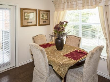 Dining room with gold embroidered table cloth, two photos mounted on a wall, curtains, and a window overlooking a lush green yard