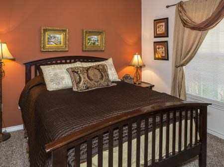 Bedroom with an orange accent wall, four photos on the wall, decorative tan curtains, and a side table with a lamp