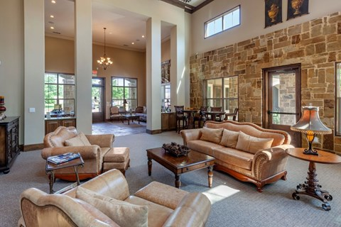 Clubhouse interior with tall ceilings, gray carpet, and tan walls. Also has leather furniture with accent pillows and windows alongside the perimeter of the room.