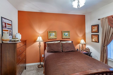 Bedroom with deep orange accent wall, dresser, stand up lamps, and decorative curtains placed over windows.