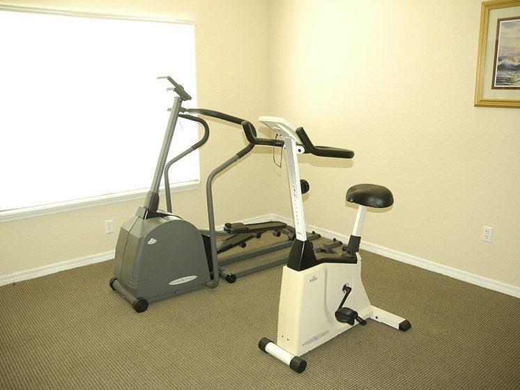 elliptical and exercise bicycle at fitness center_Dunwoodie Place Apartments Orlando, FL