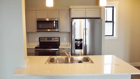Kitchen with sink, fridge, range, and microwave