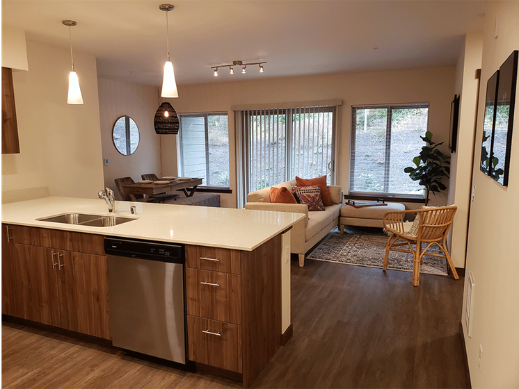 Image from kitchen into spacious living room with wood-style vinyl plank flooring.