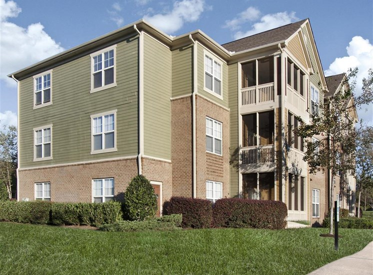 Meticulously maintained grounds with mature trees surround the soft green paint and brick exterior apartment homes at Alden Place at South Square Apartments,Durham, NC 27707