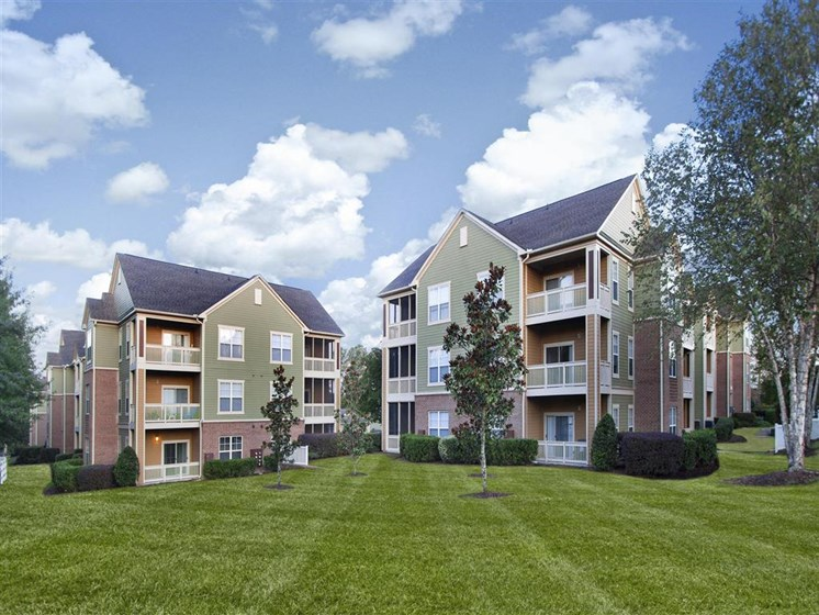 Meticulously maintained grounds with mature trees surround the soft green paint and brick exterior apartment homes at Alden Place at South Square Apartments, Durham, NC 27707
