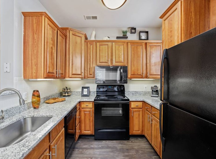 Gourmet Kitchens with Raised Panel Cabinetry, Granite Like Countertops, Black Appliance Packages and Undermount Lighting at Cambridge Square Apartments, Overland Park, KS 66211