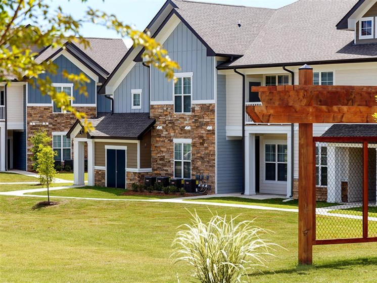 Meticulously Maintained Grounds with Mature Trees Surround the Soft Blue Paint and Brick Exterior Apartment Homes at Creekside at Providence Apartments, Mt. Juliet, TN 37122