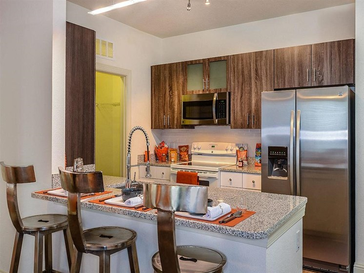 Open Floor Plan Kitchen with Wood Plank Vinyl Flooring (in Select Units) and Chef's Table-inspired Islands at EOS Apartments, Orlando, FL 32826