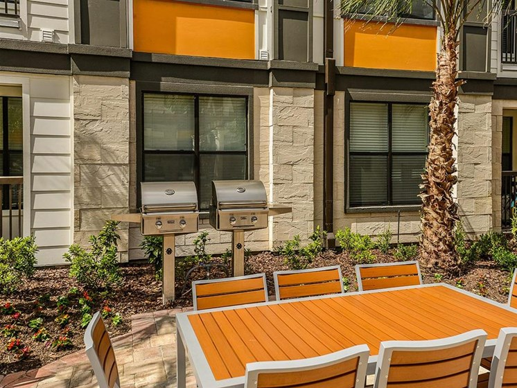 Outdoor Gourmet BBQ Gas Grilling Area with Fireplace to Enjoy a Wonderful Night with Friends and Family at EOS Apartments, Orlando, FL 32826