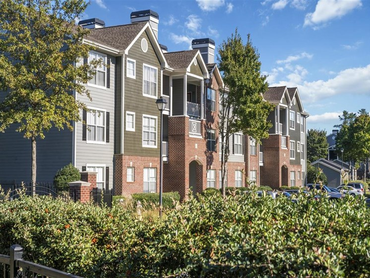 Meticulously maintained grounds with mature trees surround the soft neutral paint and brick exterior apartment homes at Estates at Crossroads, Duluth, GA 30096