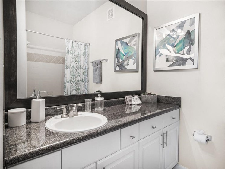 Relaxing Bathroom with Bright White Cabinets, Updated Counters, Large Mirrors and Double Vanity Sinks at Estates at Crossroads, Duluth, GA 30096