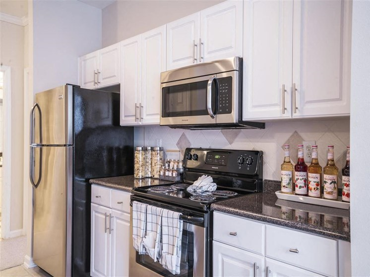 Bright White Kitchens with Stainless Steel Fridge, New Countertops, Designer Ceramic Tile Backsplash and Glass Top Ranges at Estates at Crossroads, Duluth, GA 30096