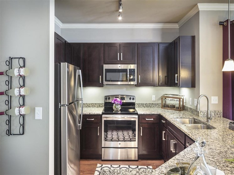 Modern Kitchen with Dark Accent Cabinetry and Granite Countertops at Greenwood Reserve Apartments, Lenexa, KS 66215