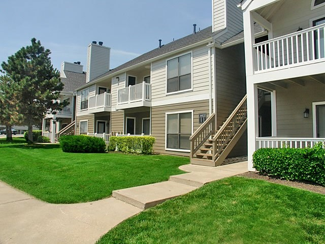 Meticulously maintained grounds with mature trees surround the soft tan paint and brick exterior apartment homes at Hampton Woods Apartments, Shawnee, KS 66217
