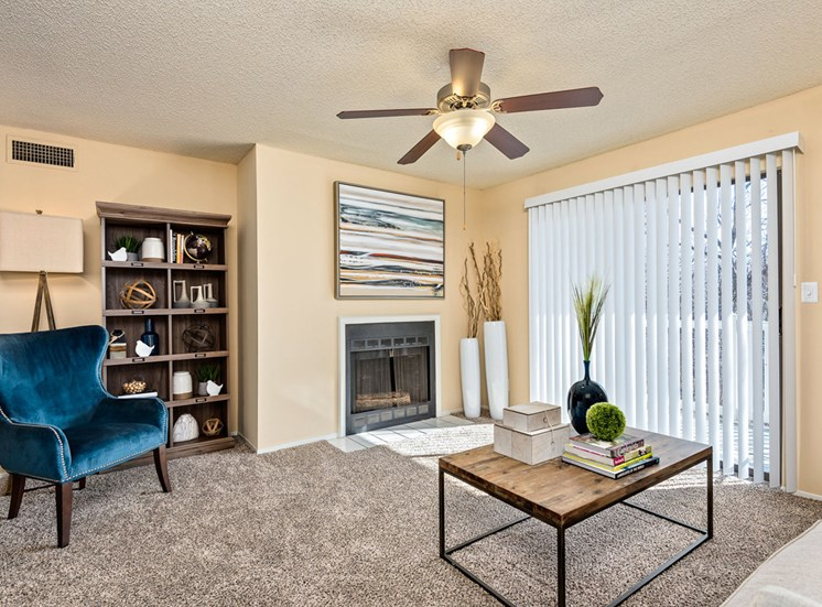 Bright Open Den Living Space with Cozy Fireplaces, Ceiling Fans and Plenty of Room for Couches and Furniture at Hampton Woods Apartments, Shawnee, KS 66217