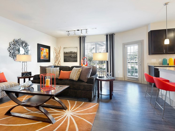 Gorgeous Modern Living Room with Elegant Crown Moulding and Wood Plank Vinyl Flooring (in Select Units) at Lone Oak Apartments, Round Rock, TX 78665