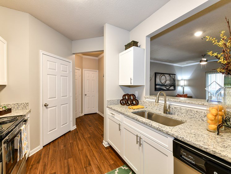 Bright White Kitchens with White Appliances, Wood Plank Vinyl Flooring, and Breakfast Bar at Madison Shelby Farms Apartments, Memphis, TN 38120