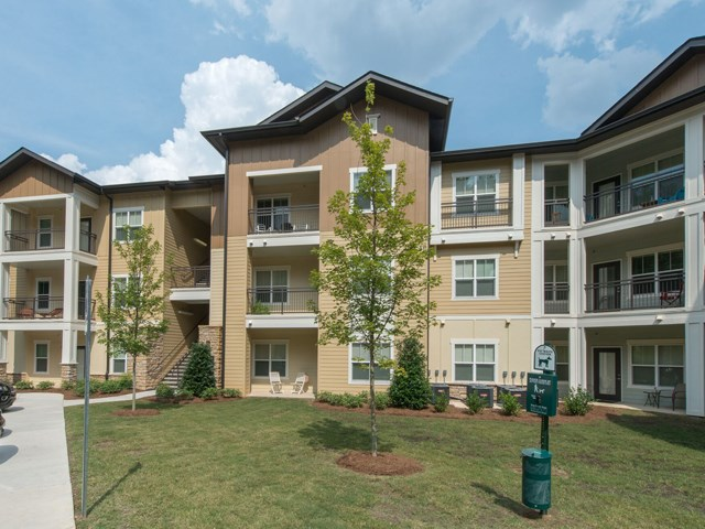 Meticulously maintained grounds with mature trees surround the soft neutral paint and brick exterior apartment homes at Moretti at Vulcan Park Apartment Homes, Homewood, AL 35209