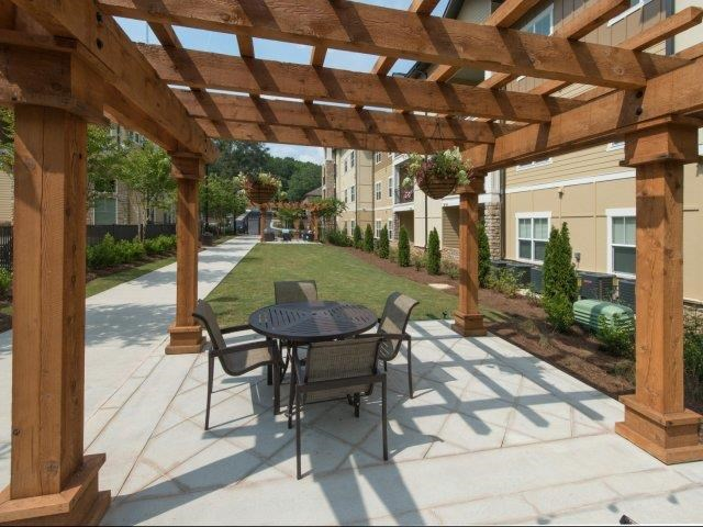 Outdoor Grill Area with Cafe Lights Above Courtyard Table and Chairs at Moretti at Vulcan Park Apartment Homes, Homewood, AL 35209