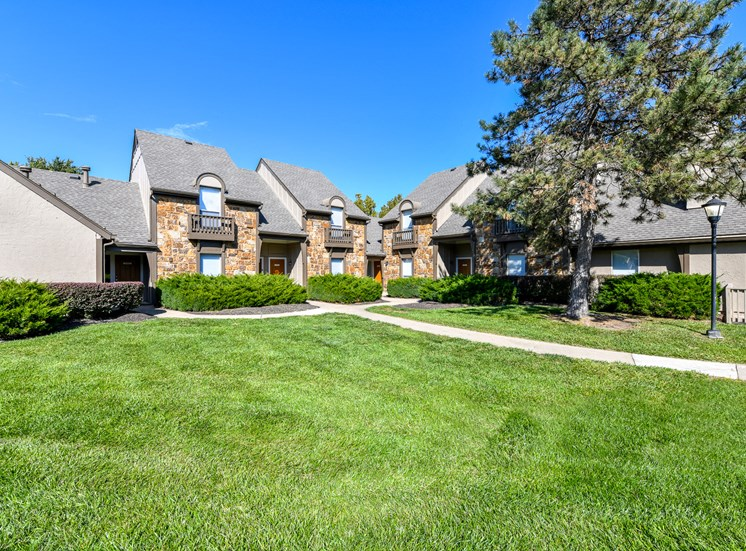 Meticulously maintained grounds with mature trees surround the soft tan paint and brick exterior apartment homes at Pointe Royal Townhome Apartments, Overland Park, KS 66213
