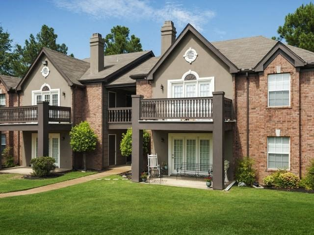 Meticulously maintained grounds with mature trees surround the soft grey paint and brick exterior apartment homes at The Addison at Collierville Apartments, Collierville, TN 38017