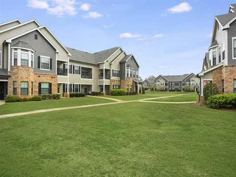Meticulously maintained grounds with mature trees surround the soft grey paint and brick exterior apartment homes at The Arlington at Eastern Shore Apartments, Spanish Fort, AL 36527
