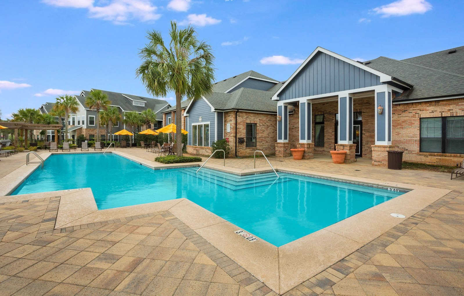 Oversized Pool with Large Sun Deck surround by Palm Trees and Comfortable Lounge Chairs at The Arlington at Eastern Shore Apartments, Spanish Fort, AL 36527
