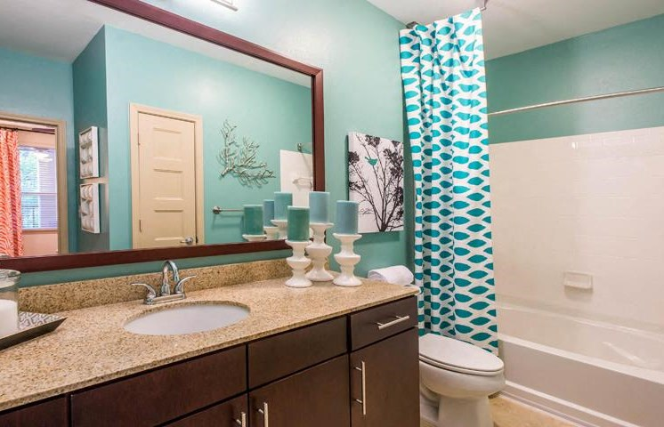 Relax after a long day in your bathroom with Contoured Oversized Tubs, new cabinets, wood plank flooring at Twenty25 Barrett Apartments, Kennesaw, GA 30144