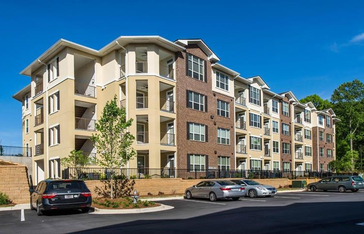 Meticulously maintained grounds with mature trees surround the soft neutral paint and brick exterior apartment homes at Twenty25 Barrett Apartments, Kennesaw, GA 30144