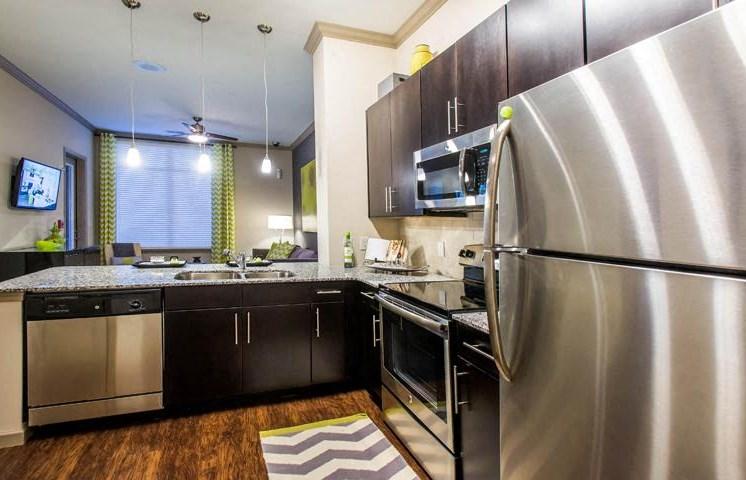 Sleek, Modern Kitchens with Energy Star Stainless Steel Appliances, Toffee & Espresso Cabinetry, Tile Backsplash & Plank Flooring at Twenty25 Barrett Apartments, Kennesaw, GA 30144