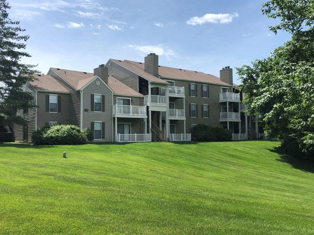 Meticulously maintained grounds with mature trees surround the soft grey paint and brick exterior apartment homes at 15Seventy Chesterfield Apartment Homes, Chesterfield, MO 63017